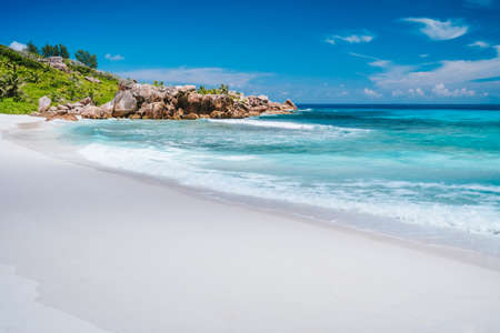 Ocean waves, pristine blue color lagoon and granite rocks on Anse Coco beach, La Digue Island, Seychelles.