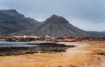 Mysterious landscape of sandy coastline with fisher village and black volcanic mountains in background. Baia Das Gatas. North of Calhau, Sao Vicente Island Cape Verde.