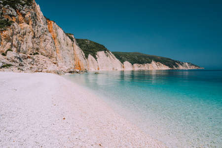 Holiday vacation scene. Fteri beach on Kefalonia Island, Greece. Most beautiful pebble beach with clear emerald blue sea water. Stock Photo