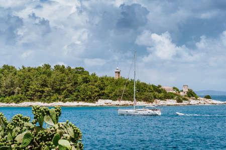 Summer holiday vacation. Kefalonia island, Greece. White sailing boat approaching port of Fiskardo.