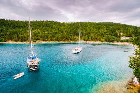 Foki beach near small town Fiskardo at Kefalonia, Ionian islands, Greece. Private yacht boats in the small lagoon. Stock Photo