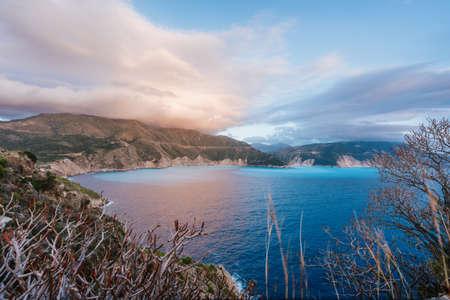 Kefalonia coastline, with rocky coast and dramatic sky on sunset. Greece vacation trip.