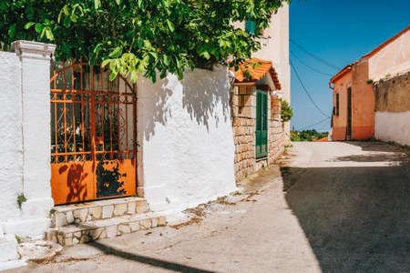 Narrow road with whitewash local houses on Kefalonia island, Greece.