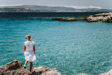 Adult female in white dress on summer vacation enjoying sea coast landscape of small beach with crystal clear blue water. Greece, Kefalonia.