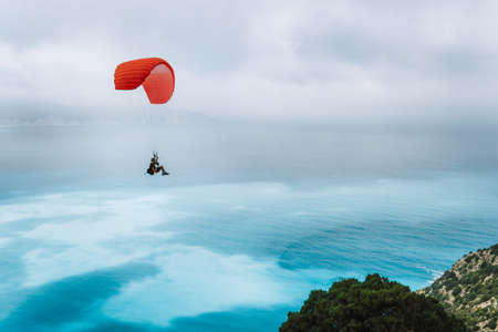 Paraglider against blue sea with foggy clouds. Kefalonia island, Greece. recreation hobby activity.