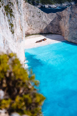Shipwreck on Navagio beach. Azure turquoise sea water and paradise sandy beach. Famous tourist visiting landmark on Zakynthos island, Greece. Stock Photo