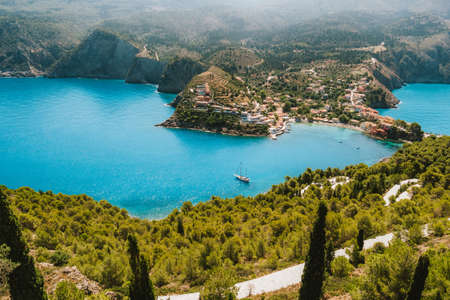 Top view to Assos village. Landmark place of Kefalonia island. Lonely white yacht at anchor in calm beautiful lagoon surrounded by pine and cypress trees. Greece. Banque d'images