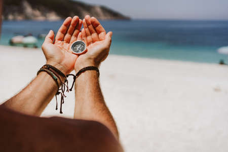 ns hand holding compass. Beach and sea in background The concept of travel, summer vacation, holiday and journey.
