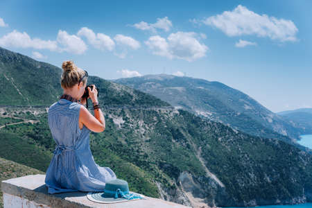 Adult female tourist with camera enjoying seascape of Kefalonia, Greece on summer holiday vacation.