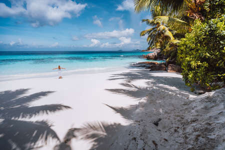 Female tourist with raised hands enjoy empty tropical beach on vacation. White powdery sand beach, palm trees and blue ocean lagoon. Exotic paradise recreation vacation concept.