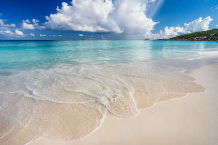 Ocean wave and cloudscape on tropical beach Grand Anse, La Digue Island, Seychelles.