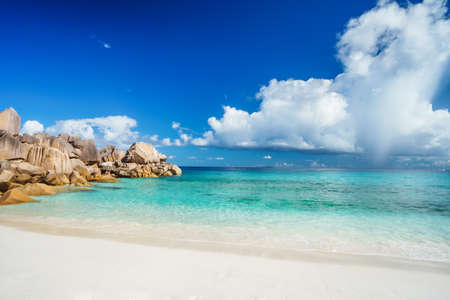 Bright sunny day at grand Anse beach at La Digue island in Seychelles. Sandy beach with blue ocean bay, white clouds in background.