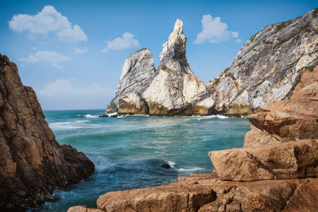 Ursa beach, Sintra, Portugal. Epic seascape of cliffs towering up from emerald green atlantic ocean. White clouds on blue sky. Summer holiday vacation background scene