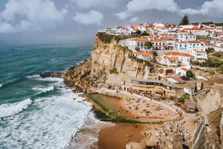 Holiday vibes on beautiful Azenhas do Mar village and wave protected beach. White chalk houses on the edge of a cliff. Bly sky and white clouds. Sintra Landmark, Portugal, Europe.