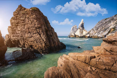 Ursa beach, Sintra, Portugal. Epic seascape of sea stack cliffs towering up from emerald green atlantic ocean. White clouds on blue sky. Summer holiday vacation background scene