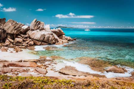 Grand L Anse, La Digue, Seychelles. Tropical coastline with hidden beach, unique granite rocks and lonely sail boat in blue ocean