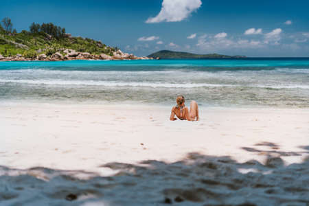 Young tanned woman enjoying tropical sandy beach Anse Cocos at La Digue Island, Seychelles