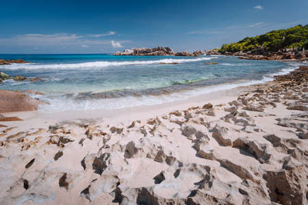 Tropical old coral coastline of remote beach with unique granite rocks, of Grand L Anse, La Digue, Seychelles