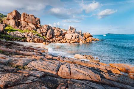 Beautiful Grand L Anse beach, La Digue, Seychelles. Tropical ocean coast, unique granite rocks and lonely sail boat on sea in sunset warm evening light Reklamní fotografie