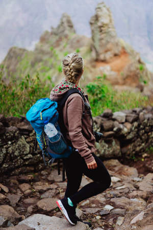 Santo Antao Island Cape Verde. Female tourist with blue backpack on hike enjoying view to Caculi valley from Corda