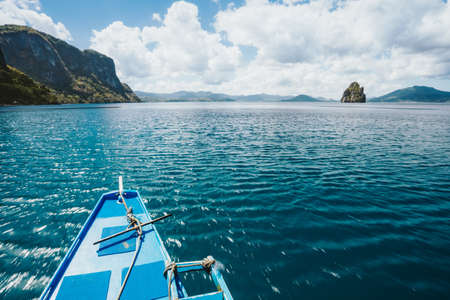 Island hopping Tour boat hover over blue ocean between exotic islands on excursion trip exploring Bacuit archipelago, El Nido, Philippines