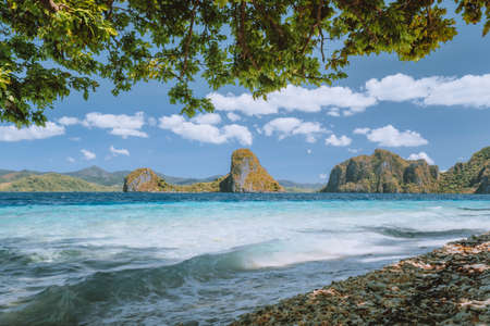 Palawan well known places. Palm trees and lonely island hopping tour boat on empty Ipil beach of tropical Pinagbuyutan, Philippines.