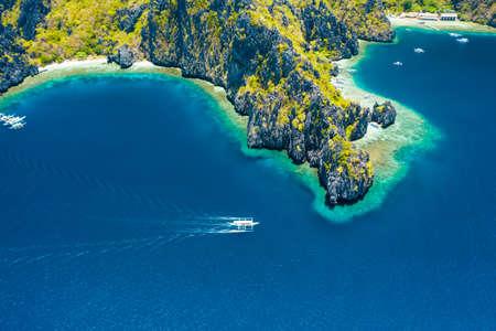 Aerial drone view of white boat in open sea, tropical island and beach of Miniloc Island. El Nido, Palawan island, Philippines. Standard-Bild