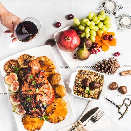 Haunch of gebratenes Spanferkel mit Maniokmehl, Früchte, Granatäpfel, Trauben und Hand Glas Wein