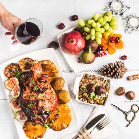 haunch of roasted suckling pig with manioc flour, fruits, pomegranates, grapes and hand holding glass of wine Stock Photo