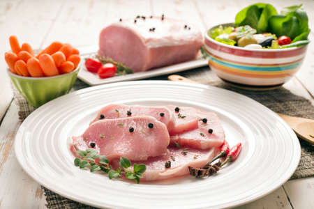 pork tenderloin, piece and slices, salad bowl and carrots