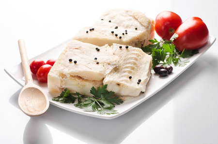 codfish: codfish with tomatoes and pepper on the plate