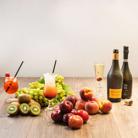 table with fruits and drinks. Peach, plum, kiwi and grape Stock Photo