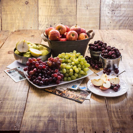 Pears, apples, plums and grapes in the basket and plate Stock Photo
