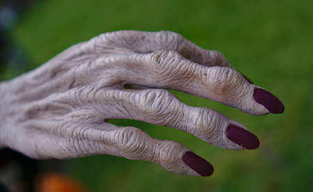 Old wrinkled finger with long fingernails in red nail polish color Imagens