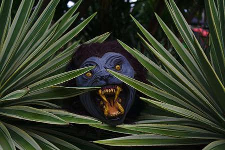 Loup-garou au visage bleu violet et aux dents jaunes pointues se cachant derrière les plantes Banque d'images
