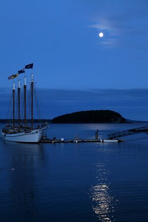 Sail boat anchored in a harbor at full monn with moonlight reflecting from the ocean