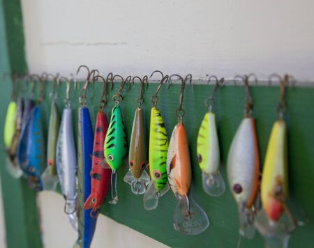 tackle: colection of artificial fishing lures hanged from a wall