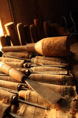 gouge: colection of carpenter chisels in the front window on an old wood working table Stock Photo