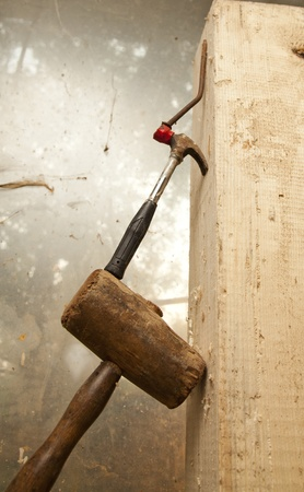 hammer and nail  on wood chunck on top of each other Stock Photo