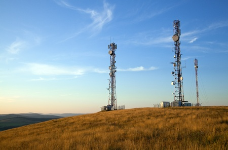 communication towers on top of hill with blue sky background Stock Photo
