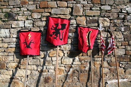 war banners and spears next to a stone wall