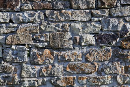 old stone wall background with moss and green spots