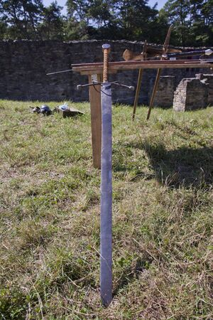 isolated medieval knoght longsword on grass near wall