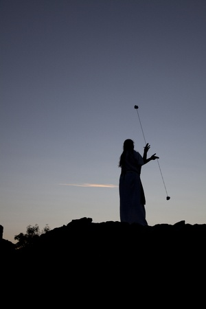 siluette of a woman playing with poi on a castle wall at sunset Stock Photo