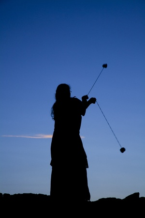 young woman playing with poi on a wall at sunset