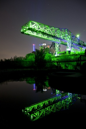 shot of industrial bridge in germany at night with reflection in water
