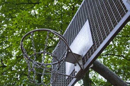basketball hoop made out of metal with green trees on the backgound Editorial