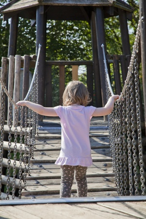 small baby girl balancing on a wooden bridge