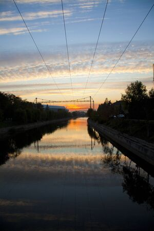 sunset over water and cables shot made from a bridge over the somes river in romania