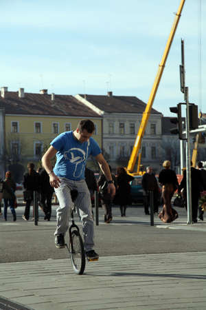 young man  riding a monocycle on a street in a crowded city